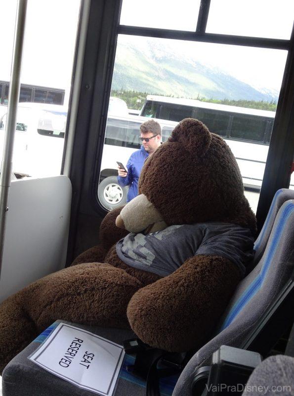 Foto de um urso de pelúcia gigante no assento do ônibus que fazia o passeio Yukon Discovery Tour