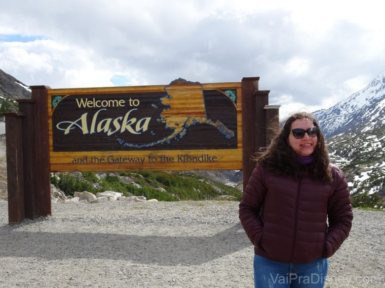 """Foto da Monica com a placa """"Welcome to Alaska"""" durante o Yukon Discovery Tour"""