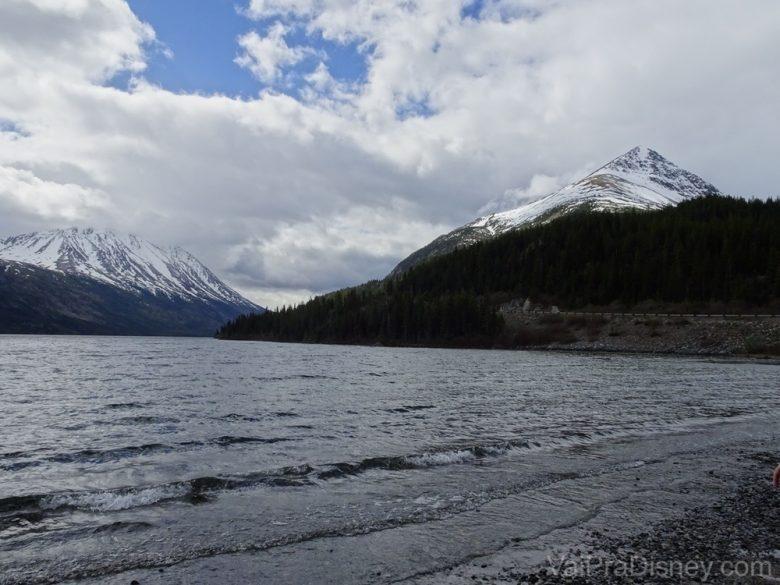 Foto do rio começando a descongelar e as montanhas ao fundo