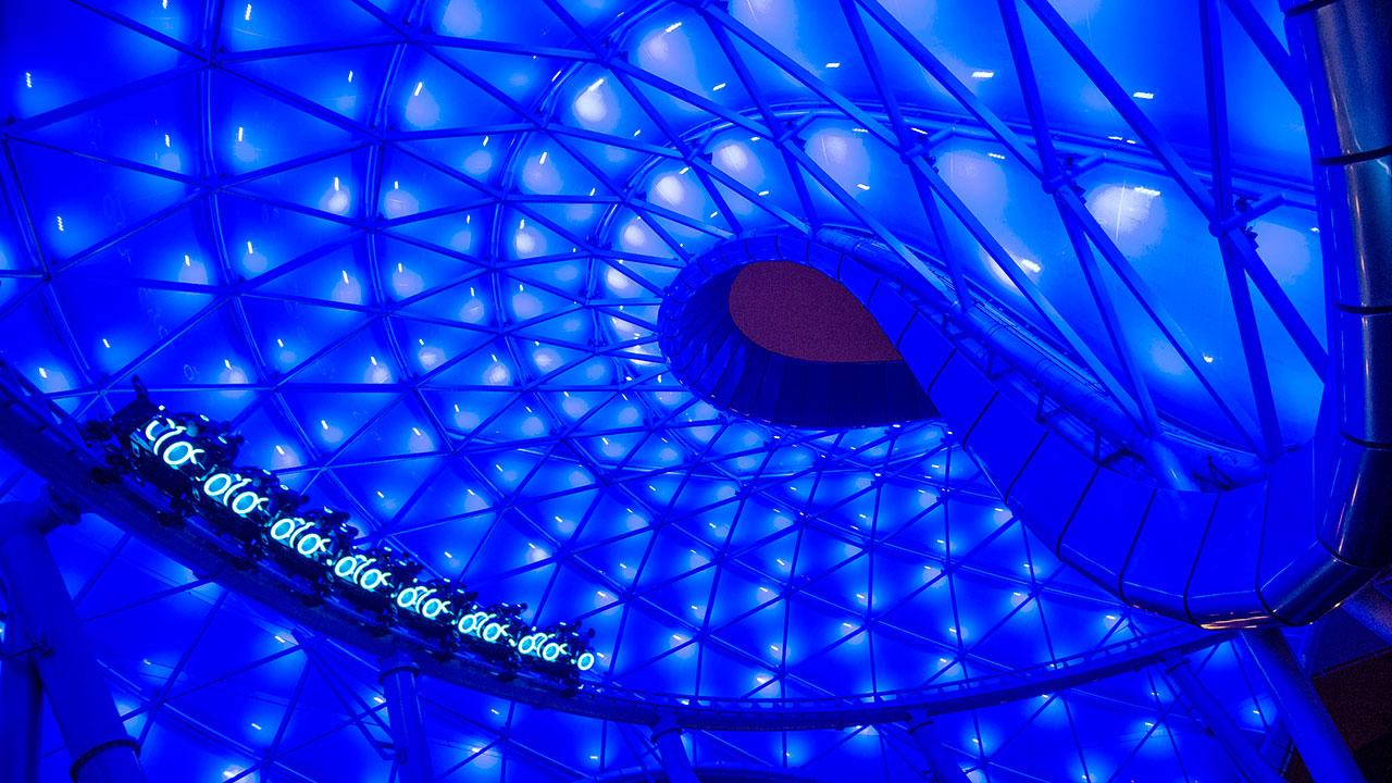 Novas atrações de Orlando - Nova montanha russa de Tron, inspirada na atração de Shanghai. Ela brilha com luzes azul-claras e o fundo é azul escuro, todo iluminado.