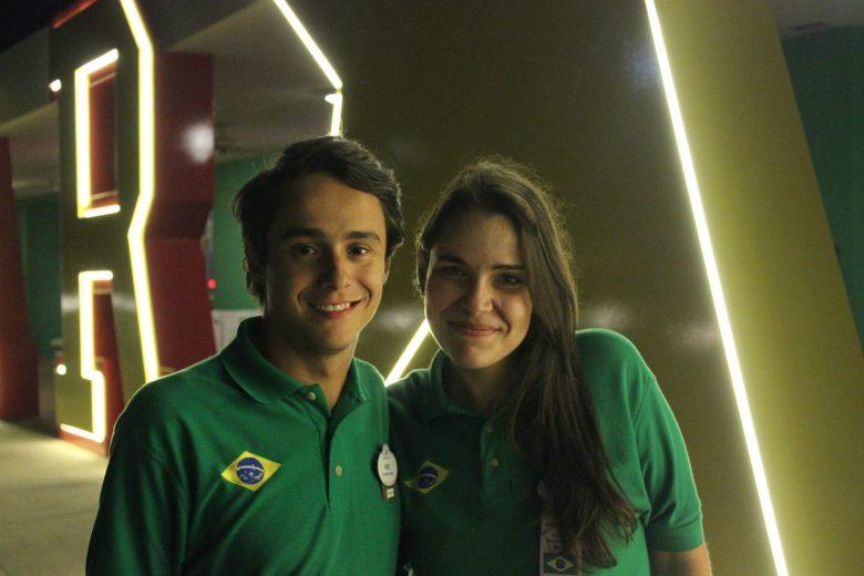 Foto da Bia e do Henrique trabalhando na Disney, no All Star, com uniformes verdes