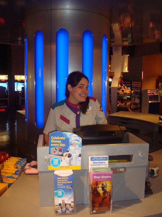 Olha a Bia aí trabalhando na Tomorrowland! Foto da Bia da equipe do VPD, com o uniforme da Disney atrás de uma caixa registradora