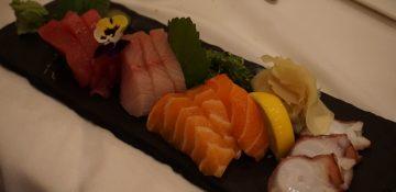 Foto de um prato de comida japonesa, com sashimi de polvo e diferentes tipos de sashimi de peixe