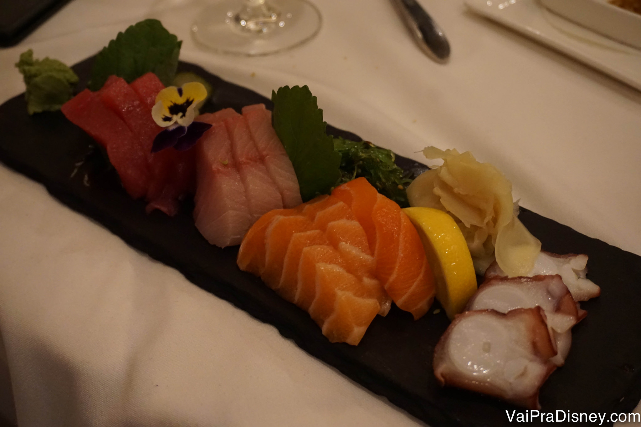 Foto de um prato de comida japonesa, com sushi, polvo e diferentes tipos de sashimi