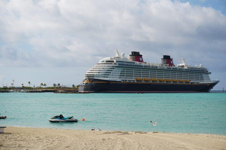 Foto do navio de cruzeiro da Disney Cruise Line perto da praia no Caribe, com o mar azul-turquesa, a areia clara e o céu claro atrás.