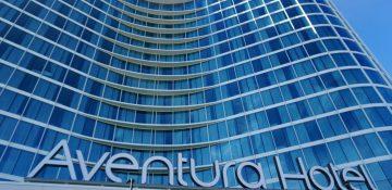 Foto da fachada do Aventura Hotel, da Universal, que é feita de vidro azul e tem um formato ondulado.