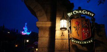 O castelo fica ainda mais bonito a noite. Foto da placa na entrada do restaurante no Magic Kingdom, durante a noite, com o castelo da Cinderela no fundo da foto. A placa iimita um brasão medieval com uma rosa, um leão e espadas.