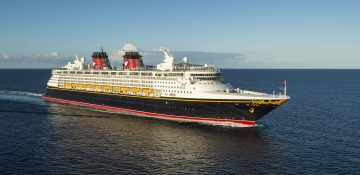 Imagem do navio de cruzeiro da Disney, o Disney Magic, em alto mar, com o céu azul ao fundo. Ele tem detalhes em amarelo e vermelho.