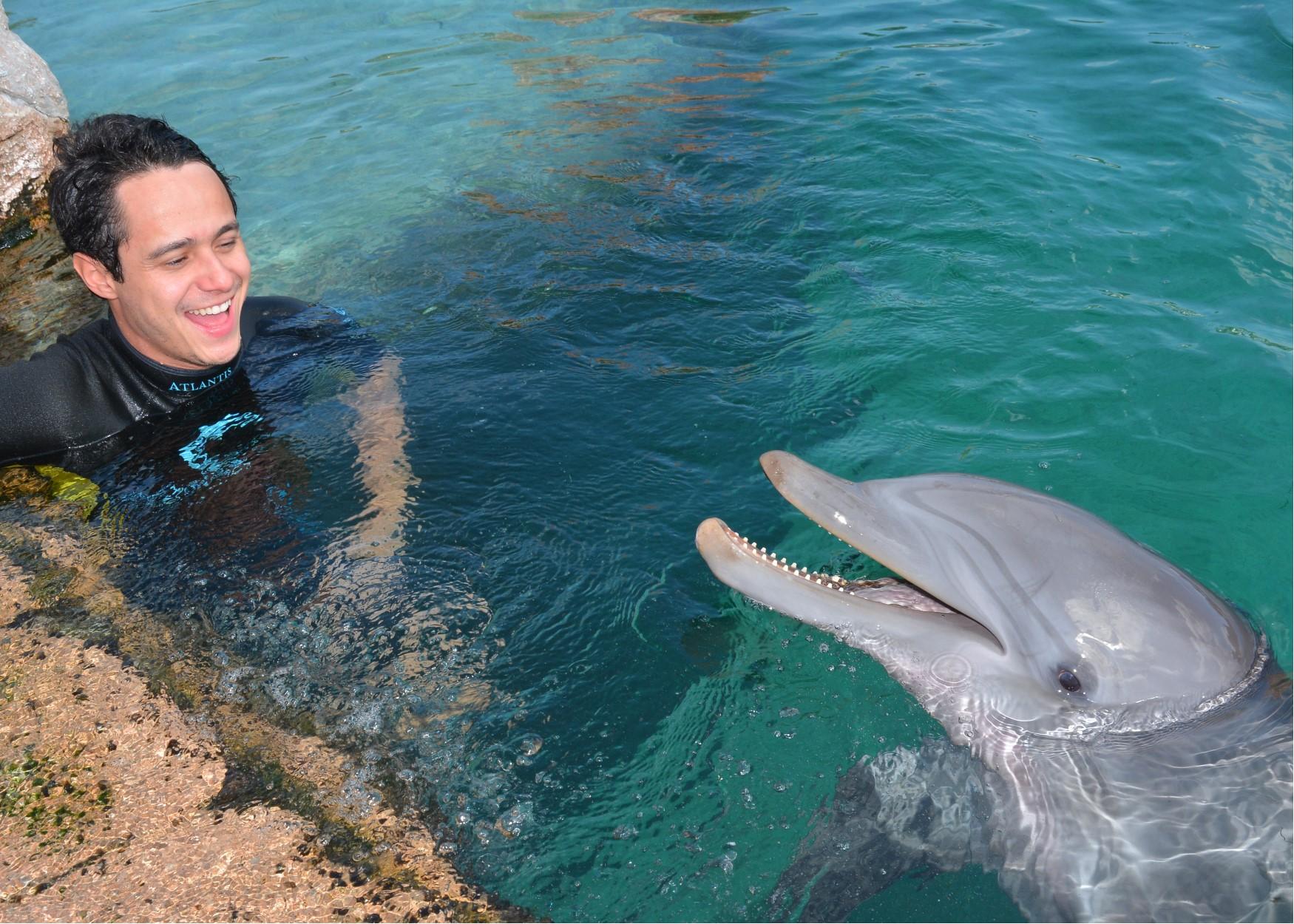 Foto do Henrique com o golfinho durante o cruzeiro da Disney, no Atlantis das Bahamas