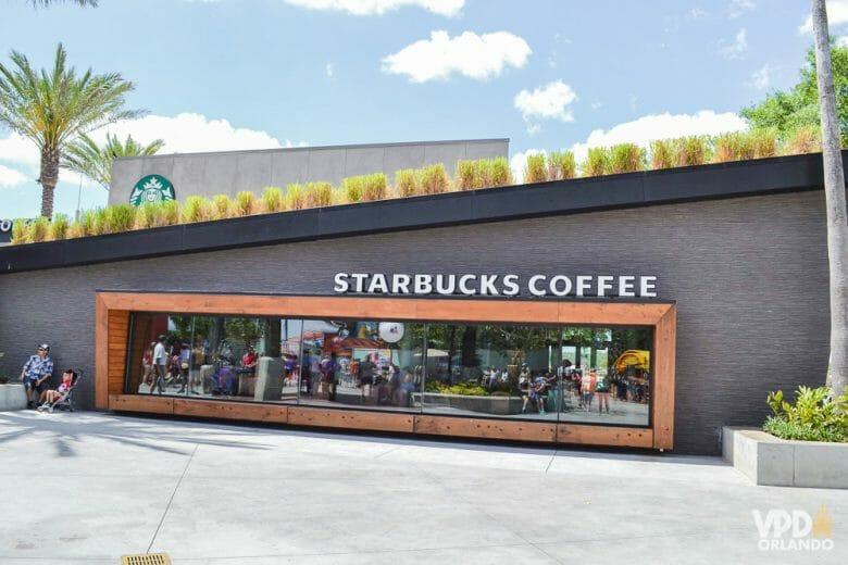 O Starbucks sempre tem Wi-Fi gratuito pra se comunicar. Foto da fachada de uma unidade da Starbucks em Orlando, com diversos visitantes dentro visíveis através dos vidros.