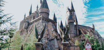 Foto do castelo de Hogwarts, que fica na Universal, com o céu azul ao fundo e alguns visitantes entrando.