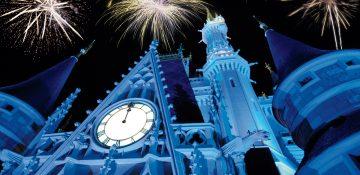 Foto do castelo da Cinderela iluminado em azul durante o show de fogos de Ano Novo no Magic Kingdom. É possível ver alguns fogos no céu acima do castelo.