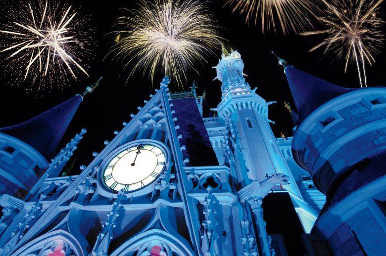 Os fogos de ano novo do Magic Kingdom. Um espetáculo imperdível. Foto: Divulgação Disney Foto do castelo da Cinderela iluminado em azul durante o show de fogos de Ano Novo no Magic Kingdom. É possível ver alguns fogos no céu acima do castelo.