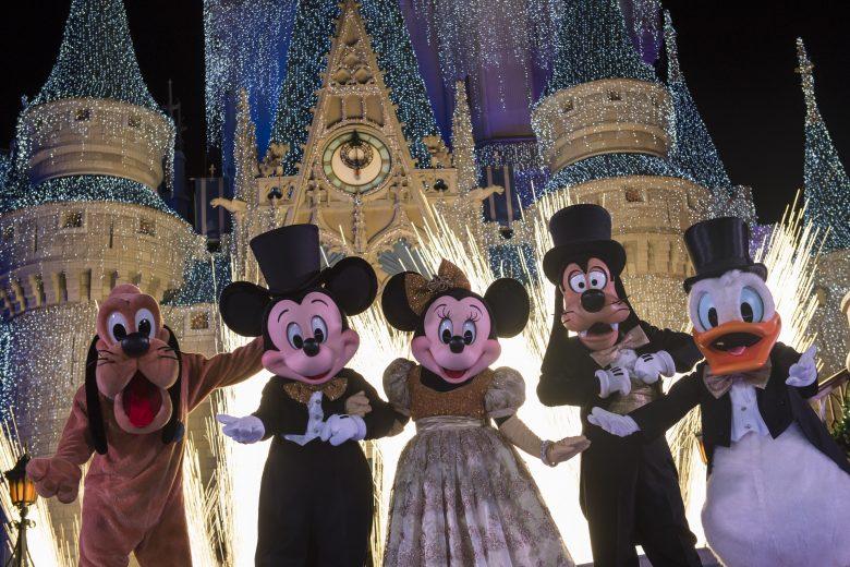 Show de ano novo no Magic Kingdom. Imagem: Divulgação Disney. Foto do show de Ano Novo do Magic Kingdom, mostrando Pluto, Mickey, Minnie, Pateta e Donald em roupas de festa em frente ao castelo da Cinderela iluminado.