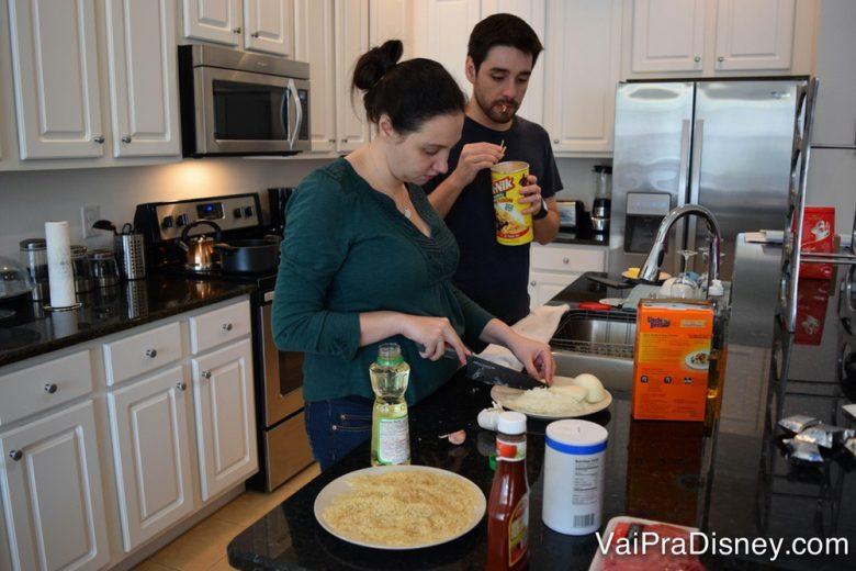Foto da Renata e do Felipe cozinhando na cozinha de uma casa alugada. É outra opção boa para quem tem criança difícil para comer