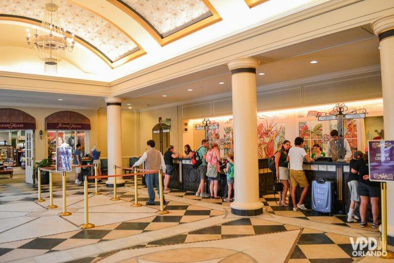 O check-in é um dos únicos momentos onde é necessário interagir em inglês no hotel. Foto da recepção de um hotel, com visitantes fazendo check-in