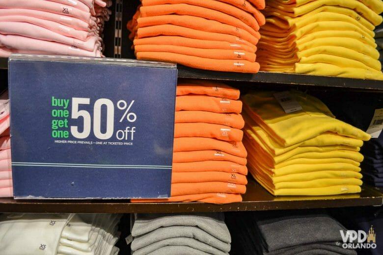 """Fique de olho nas letras menores nas placas de promoções. Foto de camisetas em promoção, com uma placa que diz """"buy one, get one 50% off"""""""