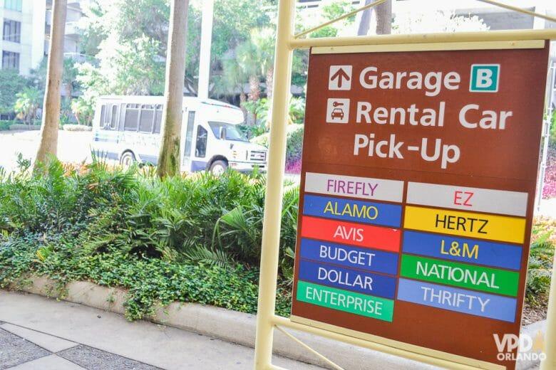"""O inglês pode ser necessário na hora de retirar o carro alugado! Foto da placa das locadoras de carro no aeroporto, com as palavras """"garage"""" e """"rental car pick-up"""" e a lista de locadoras abaixo"""
