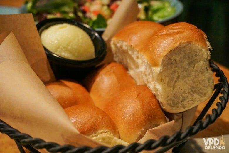 Nos EUA, esse pãozinho com manteiga de entrada é cortesia :). Foto da cesta de pães com a manteiga ao lado em um restaurante