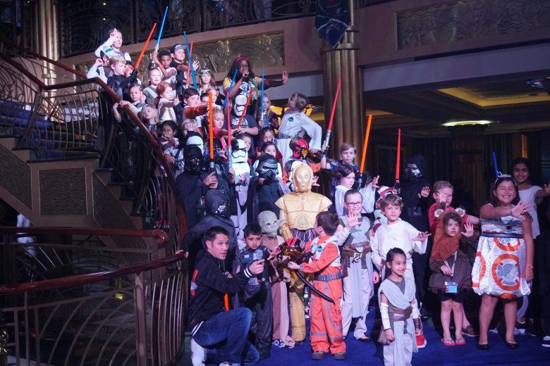 Foto de um cruzeiro temático de Star Wars com os personagens e muitas crianças fantasiadas no átrio do navio