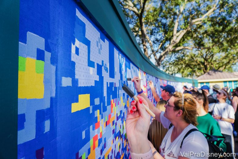 Pessoas pintando o mural com várias cores no Festival of the Arts do Epcot