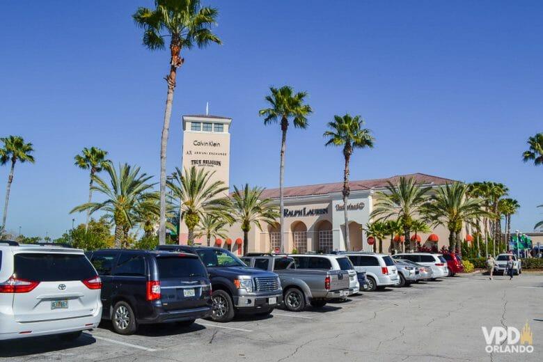Outlet é sempre bom, mas no feriado em janeiro tem mais desconto ainda! Imagem do estacionamento do Premium Outlet em Orlando, com carros enfileirados e o céu azul ao fundo.