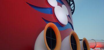 Foto de um detalhe do navio da Disney Cruise Line com o Mickey em branco e o fundo pintado de azul e vermelho.