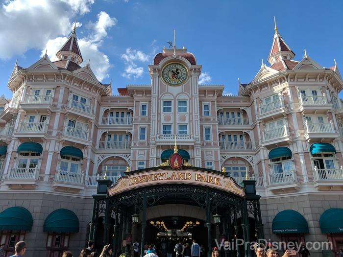 Foto da entrada da Disneyland Paris, com uma construção pintada de rosa no estilo da Main Street com um relógio do Mickey em seu centro.