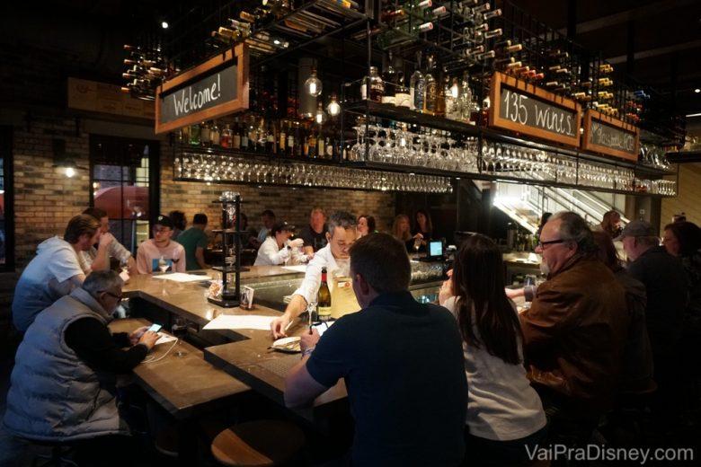 Foto do bar no interior do restaurante, com diversos visitantes sentados