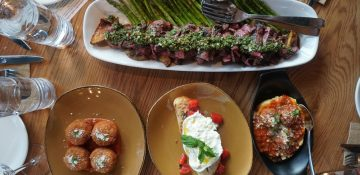 Foto da comida no Wine Bar George, com burrata e uma Skirt Steak, carne com chimichurri, batatas assadas e aspargos