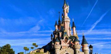 Foto do castelo da Bela Adormecida, na Disneyland de Paris, com o céu azul ao fundo.