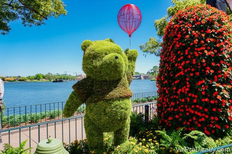 Foto da topiária do Pooh com um balão durante o Flower & Garden, com o lago do Epcot ao fundo