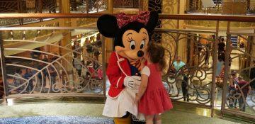 Foto da Minnie recebendo um beijo de uma criança durante um dos cruzeiros da Disney