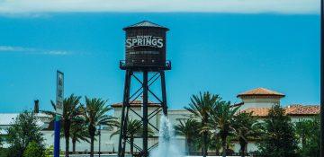 Foto da caixa d'água de Disney Springs, que leva o nome do local, com as árvores ao redor, uma fonte espirrando água mais embaixo e o céu azul ao fundo.