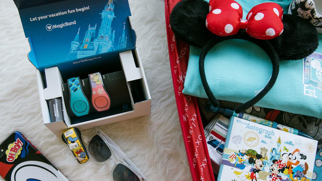 Existe também o opcional de pagar um pouco a mais por uma MagicBand mais elaborada, com desenhos e personagens. Foto de alguns itens sobre a cama: três MagicBands personalizadas, orelhinhas da Minnie, uma capinha de celular personalizada e óculos de sol.