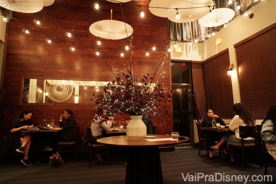 Foto da área do fundo do restaurante, bem iluminada e com poucas mesas