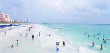 Foto da praia de Clearwater, na Flórida, mostrando a areia, o mar transparente, o céu claro e alguns visitantes passeando