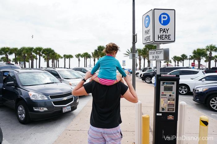 Foto do Felipe com a Júlia nos ombros no estacionamento da praia