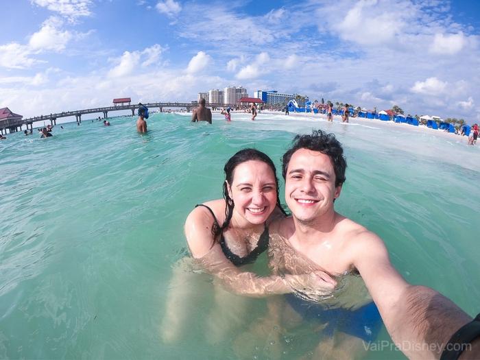 Foto da Renata e do Henrique no mar, com a areia e as pessoas ao fundo