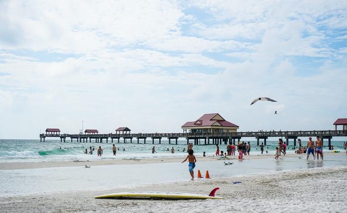 Foto da praia de Clearwater, com gaivotas voando e um píer ao fundo
