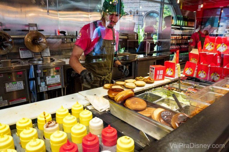 Foto da comida sendo preparada do outro lado do vidro no Chicken Guy