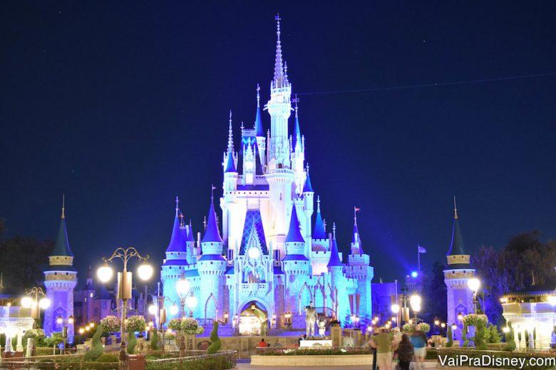 Foto do castelo da Cinderela no Magic Kingdom, iluminado em azul com o céu noturno atrás e todas as luzes da Main Street já acesas