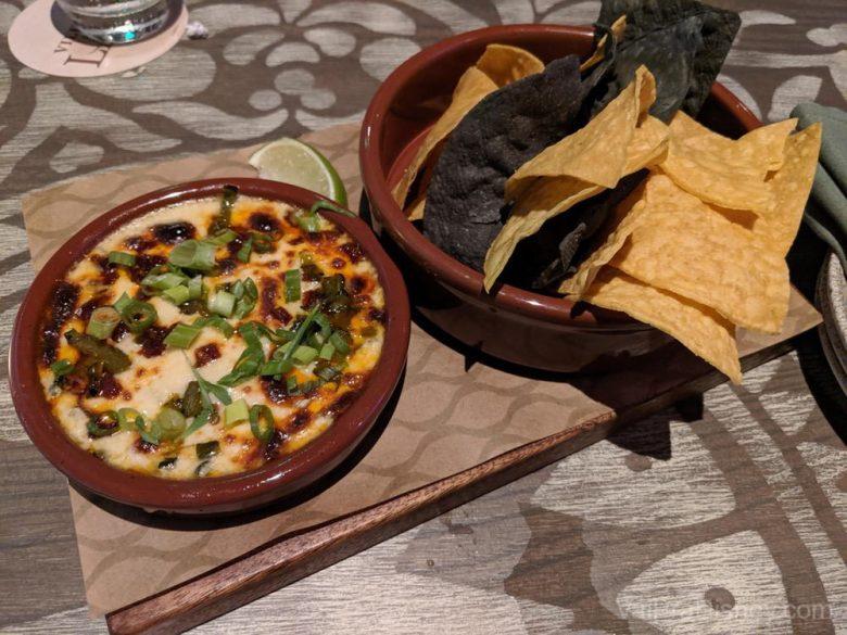 Foto da comida no Three Bridges - nachos e molho de queijo.