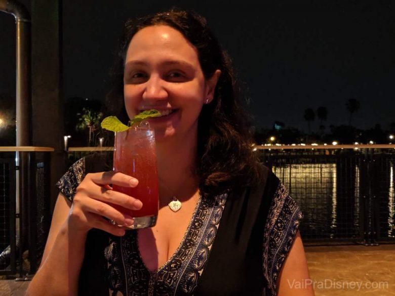 Foto da Renata sorrindo com um drink na mão no Three Bridges Bar & Grill at Villa del Lago, com um lago ao fundo