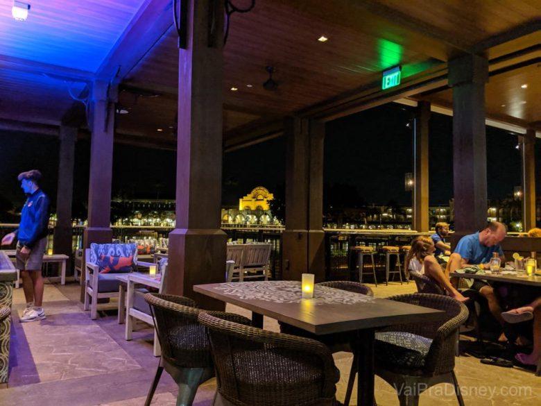 Foto do interior do Three Bridges Bar & Grill at Villa del Lago, todo de madeira, com cadeiras confortáveis e a vista do lago ao fundo.