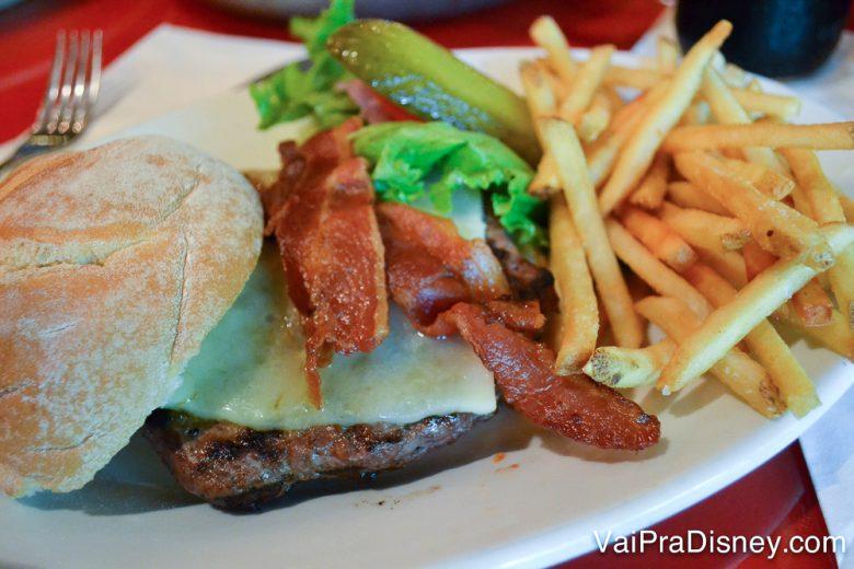 Foto do hambúrguer do restaurante, com bacon e batatas fritas ao lado