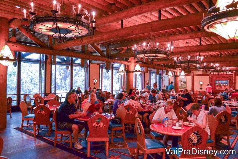 Foto do interior do restaurante, amplo, cheio de mesas com visitantes e decorado todo em madeira