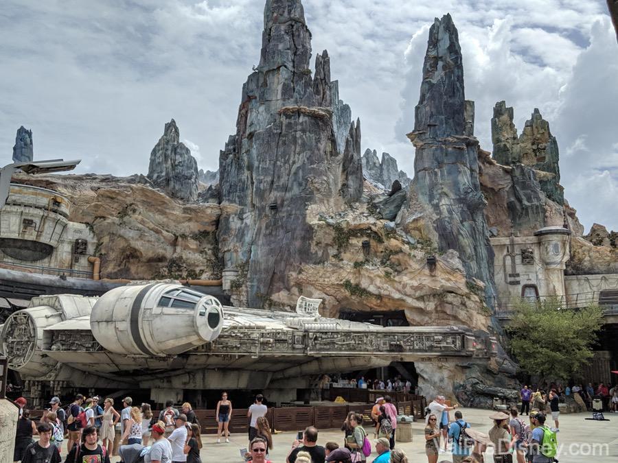 Foto da Star Wars Galaxy's Edge durante o dia, com as montanhas de Batuu ao fundo e a Millenium Falcon mais perto dos visitantes.