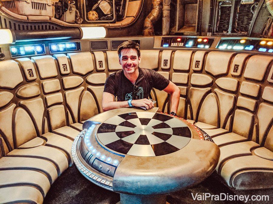 Foto do Felipe no interior da Millenium Falcon, sentado na famosa mesa de xadrez holográfico