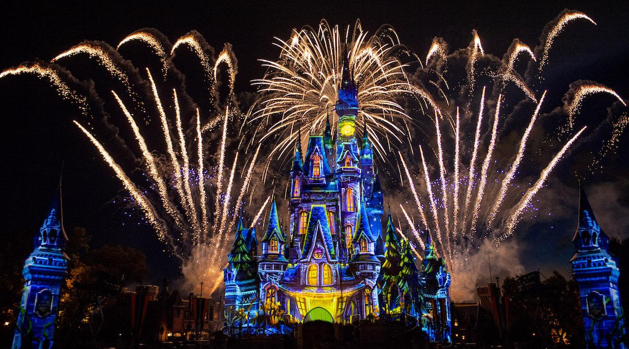 Imagem do show de fogos da Festa de Halloween da Disney, com o castelo da Cinderela iluminado por projeções coloridas.